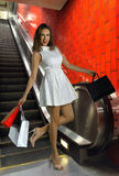 Young attractive woman in white dress. With shopping bags at fashion mall escalator Stock Photo