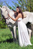 Young attractive woman in white dress with white horse royalty free stock photography