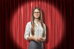 Young attractive woman in white office shirt, grey skirt and glasses, standing in spotlight against red stage curtain. stock photography