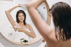 Young attractive woman in white towel shaving armpits with plastic razor after shower, reflection in mirror in stylish bathroom. With greenery. Skin and body royalty free stock photography