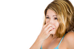 Young attractive woman who covers her nose, looks away, something stinks Royalty Free Stock Images