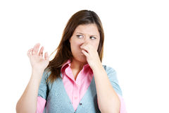 Young attractive woman who covers her nose, looks away, something stinks Stock Photos