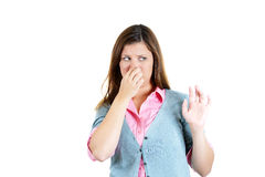 Young attractive woman who covers her nose, looks away, something stinks Stock Image
