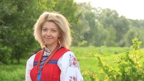 Young attractive woman, woman in folk ethnic dress smiling, wind stock video