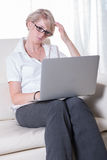 Young attractive woman working with laptop on couch Royalty Free Stock Image