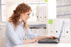 Young attractive woman working on laptop in office Royalty Free Stock Image