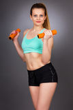 Young attractive woman working out with dumbbells Stock Photography