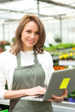 Young attractive woman working at the plants nursery using lapto Royalty Free Stock Images