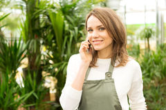 Young attractive woman working at the plants nursery using smart Royalty Free Stock Photo