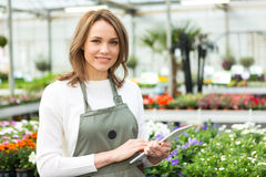 Young attractive woman working at the plants nursery using table Stock Photo