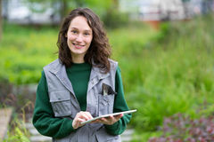 Young attractive woman working in a public garden using tablet. View of a Young attractive woman working in a public garden using tablet Stock Photography