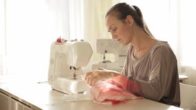 Young attractive woman working at sewing machine stock video footage