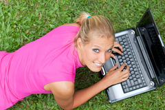 Young attractive woman works on her laptop Royalty Free Stock Image