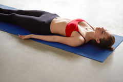 Young attractive woman in yoga outfit rests on the floor in savasana Royalty Free Stock Images