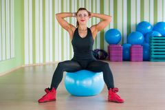 Young attractive womansits on the ball in fitness in the gym wit Stock Photos