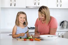 Young attractive woman cooking together with her sweet beautiful blond little 6 or 7 years old daughter smiling happy preparing sa stock photography