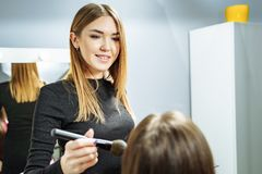 Young attractive woman makeup artist applying makeup model royalty free stock photography