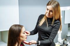 Young attractive woman makeup artist applying makeup model royalty free stock photos