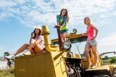 Young attractive women on old big tractor Royalty Free Stock Photo