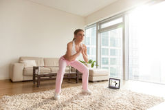 Woman making deep squats in living room at home. Young attractive women in sportswear making deep sumo squats in living room while watching fitness online video Stock Photography