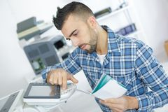 Young attractive worker man working using printmaking device royalty free stock images