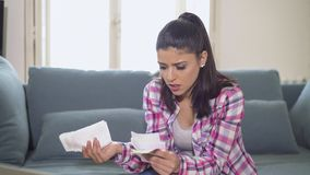 Young attractive and worried hispanic woman checking bills bank papers expenses and monthly payments in stress at apartment living. Room couch in domestic Royalty Free Stock Photography