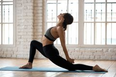 Young attractive yogi woman practicing yoga, Horse rider pose. Young sporty attractive woman practicing yoga, doing Horse rider exercise, anjaneyasana pose royalty free stock photography