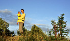 Young Attractive young mother holding a little girl in her arms at sunset light.  Walk in the autumn warm evening outdoors at suns Stock Images