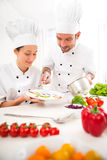 Young attractives professionals chefs cooking together Royalty Free Stock Photography