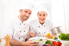 Young attractives professionals chefs cooking together Stock Photos