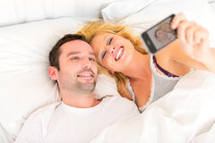 Young attracttive couple taking selfies in bed Stock Photo