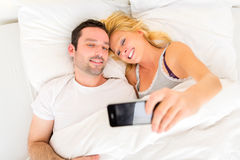 Young attracttive couple taking selfies in bed Royalty Free Stock Image