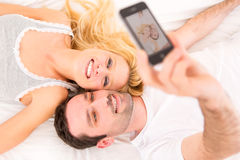 Young attracttive couple taking selfies in bed Stock Images