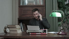 Young author typing on typewriter and being distracted by a phone call. Professional shot on BMCC RAW with high dynamic range. You can use it e.g. in your stock footage