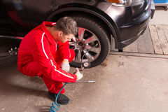 Young auto mechanic checking the air pressure of a tyre. Crouching down alongside the vehicle with the gauge from the pump in his gloved hand Royalty Free Stock Photo