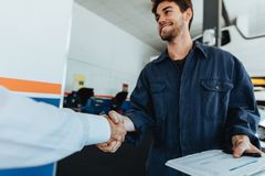 Auto mechanic shaking hands with satisfied customer. Young auto mechanic shaking hands with satisfied customer in garage. Automobile service center worker royalty free stock photography