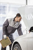 Young automobile mechanic examining car in automobile shop Stock Images