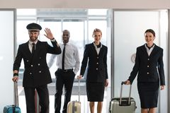 Young aviation personnel team with suitcases at airport. After flight stock image