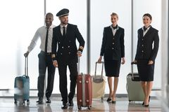 Young aviation personnel team walking by airport loggy. With suitcases stock photography
