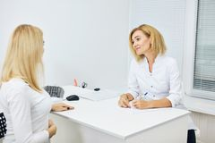 Young awesome therapist giving recomendations to a pregnant woman. Young awesome therapist giving recomendations to a pregnant women indoors. close up side view stock images