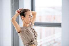 Young awesome woman ddoing a hairbun before yoga classes. Close up side view photo stock images