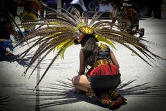 Young Aztec dancer kneels as part of her performance. Young Aztec Dancer: SULPHUR, OKLAHOMA-May 27, 2018. A young girl dressed in Aztec attire performs a Royalty Free Stock Images