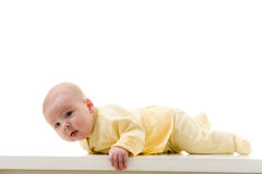 Young baby boy creeps on a table Royalty Free Stock Photos