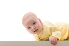 Young baby boy creeps on a table Stock Photography
