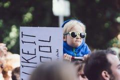 Young baby boy on dad shoulder holding demonstration sign banner