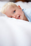 Young Baby Boy Lying In Bed Stock Photo