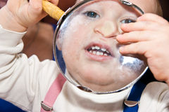 Young baby boy and magnifying glass. 2010 Stock Images