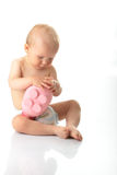 Young baby boy playing with pink piggy bank. Isolated Royalty Free Stock Photography
