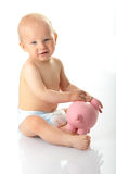 Young baby boy playing with pink piggy bank Royalty Free Stock Photos