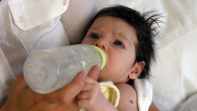 Young baby drinking from a milk bottle. At home stock video footage